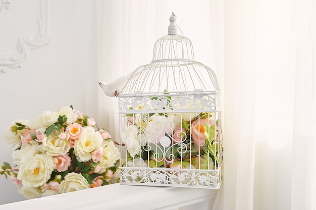 Decorative bird cage with bouquet of flowers in the interior.