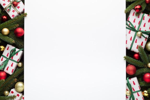 モミの枝、ギフトボックス、クリスマスボールの装飾的な境界線。クリスマスクリープの白い背景