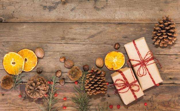 Bordo decorativo con regali e decorazioni natalizie su fondo in legno rustico