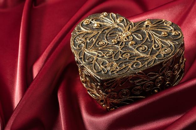 Декоративная коробка в форме сердца на красной шелковой ткани