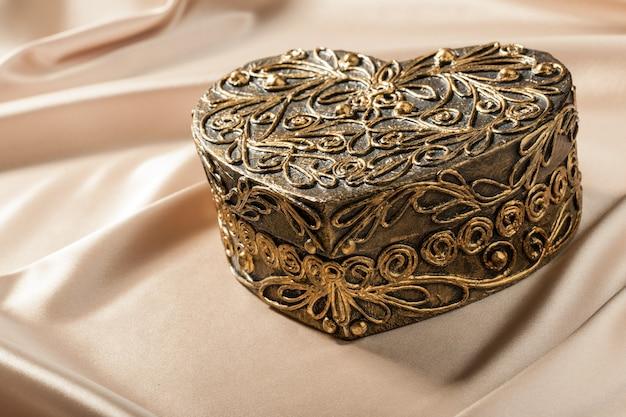 Декоративная шкатулка в форме сердца на шелковой ткани