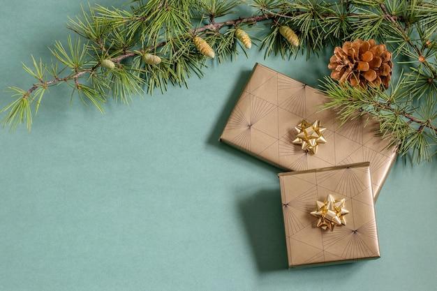 緑のお祭りの背景に装飾ボックスプレゼントとクリスマスツリーの枝