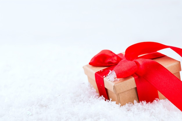 Decorative brown gift box with a large red bow standing in fresh snow