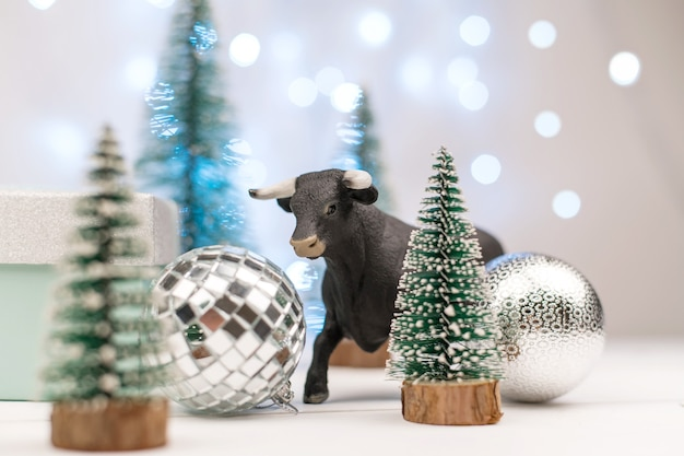 Decorative bull, symbol of the new year on the background of christmas trees and blue bokeh.
