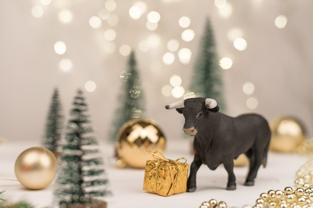 Decorative bull, symbol of the new year on the background of christmas trees and golden bokeh.