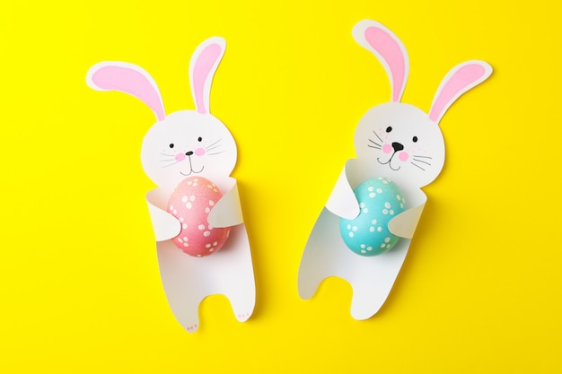 Decorative bunnies and easter eggs on yellow surface