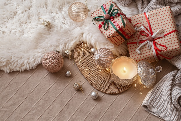 Decorative burning candle on the background of christmas gifts with cozy things and decor details close up.