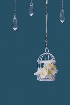 청록색 배경에 사슬에 재스민 꽃과 유리 펜던트가 있는 장식용 새장. 아름다운 축제 결혼식 개념