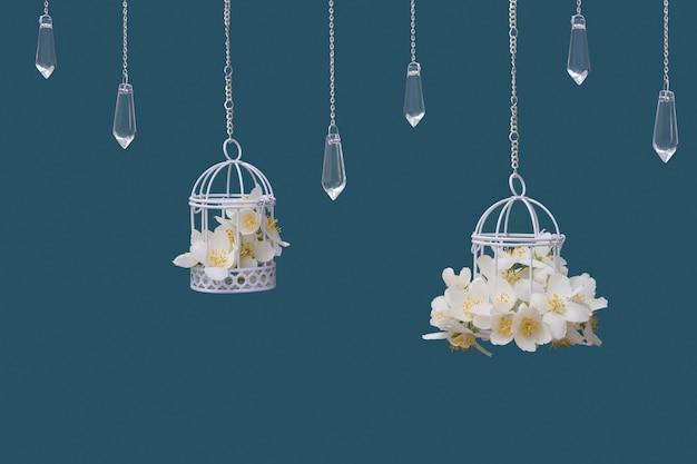 청록색 배경에 사슬에 재스민 꽃과 유리 펜던트가 달린 장식용 새장. 아름다운 축제 결혼식 개념