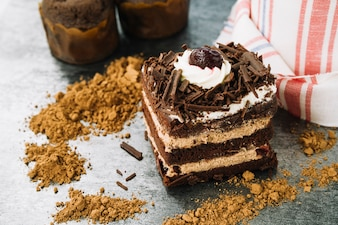 Decorative cake slice with chocolate powder on kitchen counter