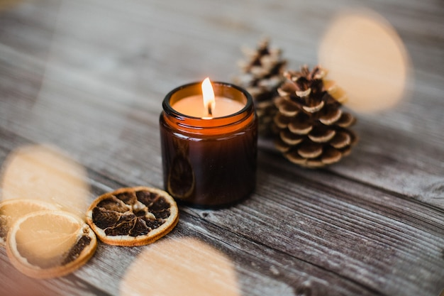 Decorative candle, dried orange slices and pine cones