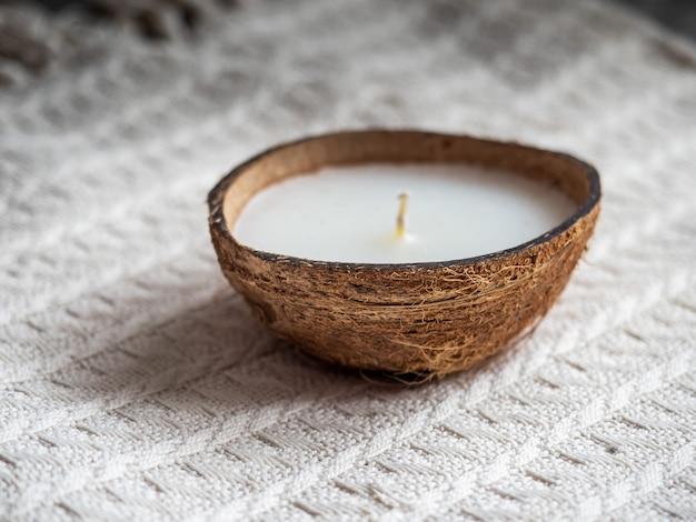 Декоративная свеча в половину кокоса на белом вязаном одеяле крупным планом