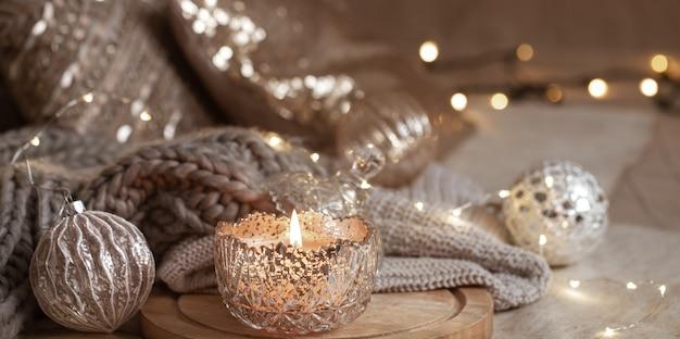 Декоративная свеча в серебряном подсвечнике на размытом фоне праздничного домашнего декора.
