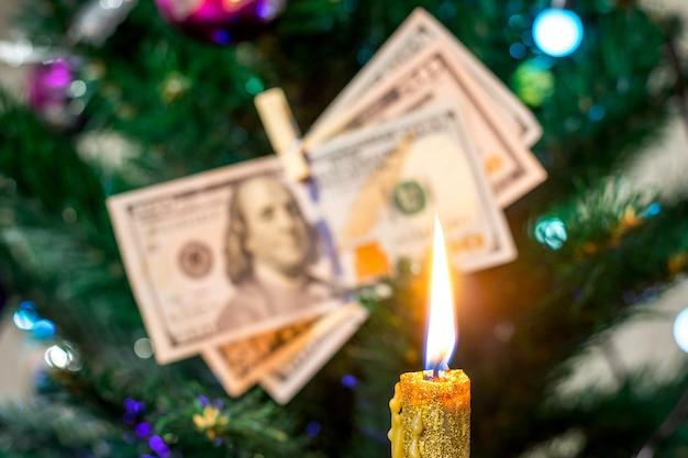Декоративная свеча на фоне елки, украшенной долларами.