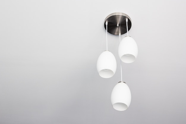 Decorative ceiling light with bare wall and copy space.