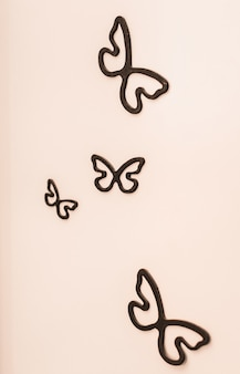Decorative ceramic black butterfly on white wall.