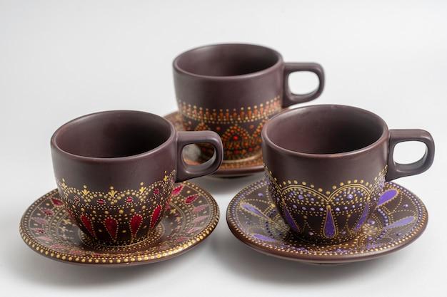 白い背景の上の装飾的なセラミック塗装のカップとソーサー、クローズアップ。アクリル絵の具、手仕事、ドット絵で描かれた装飾的な磁器のカップとソーサー