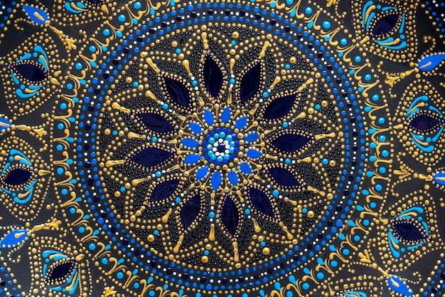 검정, 파랑 및 황금색으로 장식된 세라믹 판, 배경에 칠해진 판, 근접 촬영, 위쪽 전망. 아크릴 물감으로 칠한 디테일 도자기 접시, 수공, 도트 페인팅