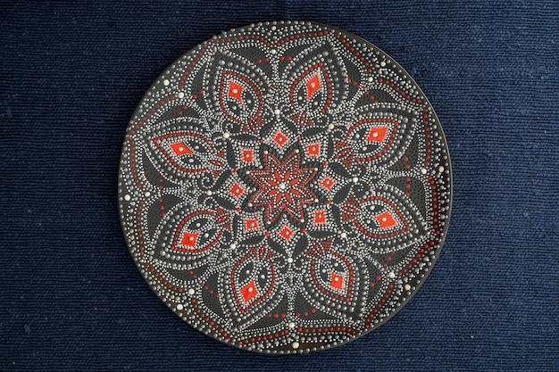 Decorative ceramic plate with black, red and golden colors, painted plate on background of fabric, closeup, top view. decorative porcelain plate painted with acrylic paints, handwork, dot painting