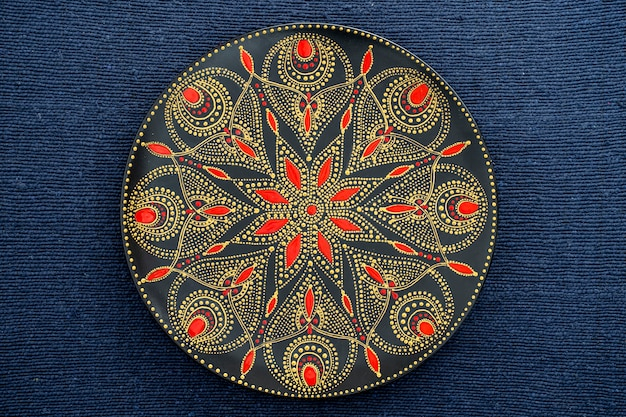 Decorative ceramic plate with black, red and golden colors