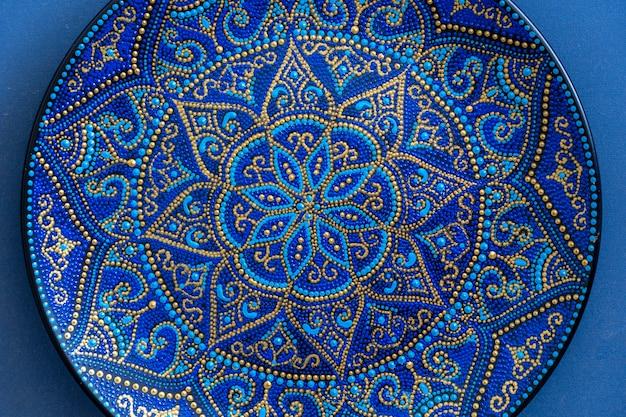 青と金色の装飾セラミックプレート、塗装プレート、クローズアップ。アクリル絵の具で描かれた装飾的な磁器プレート、手仕事