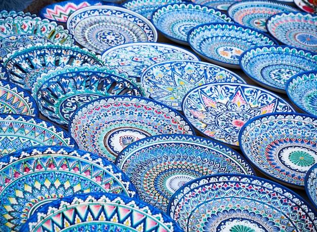 Декоративные керамические тарелки с традиционным узбекским орнаментом на уличном рынке бухары. узбекистан, центральная азия, шелковый путь