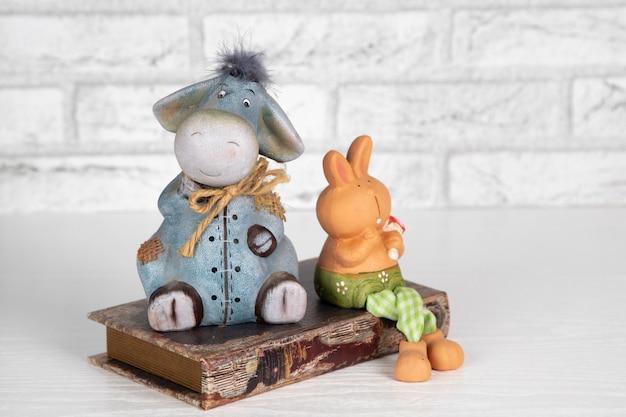 밝은 배경에 장식용 세라믹 장난감 토끼와 당나귀 돼지 저금통