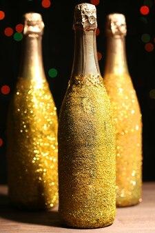 濃い色の斑点のある表面に装飾的なシャンパンボトル