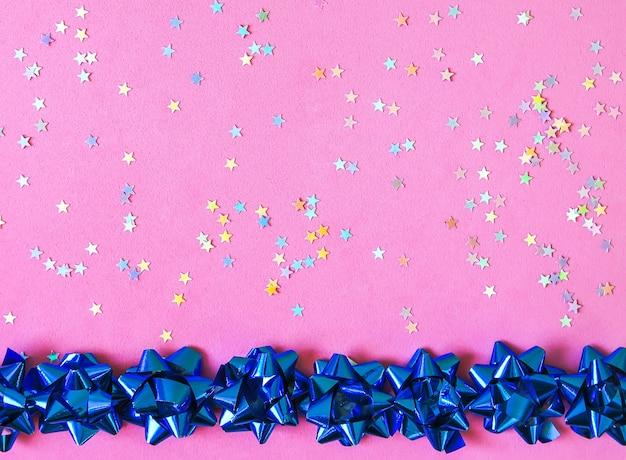 Декоративный фон рождество и новый год. праздничный шаблон. открытка с копией пространства. голубые бантики подарка и красочная мишура на зернистой розовой пастельной текстуре.