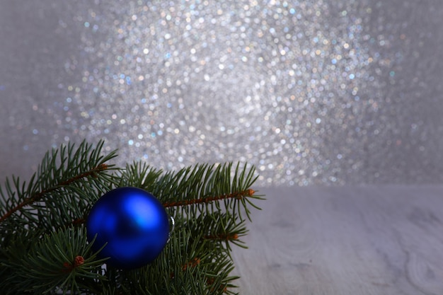 Decorative christmas background with fir branches and blue balls on the silver