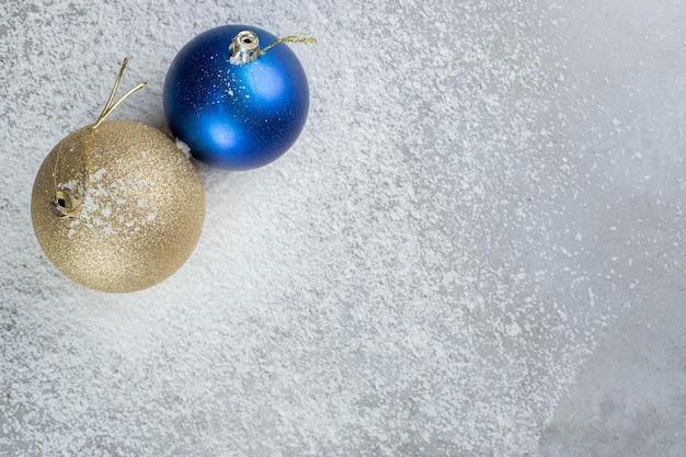 Декоративные елочные шары, сидящие в кокосовой пудре на мраморном столе.