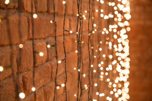 Decorative christmas garland with lanterns hanging on the brick