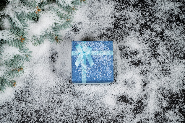 Декоративный рождественский подарок в снегу со снежинками на зимнем фоне