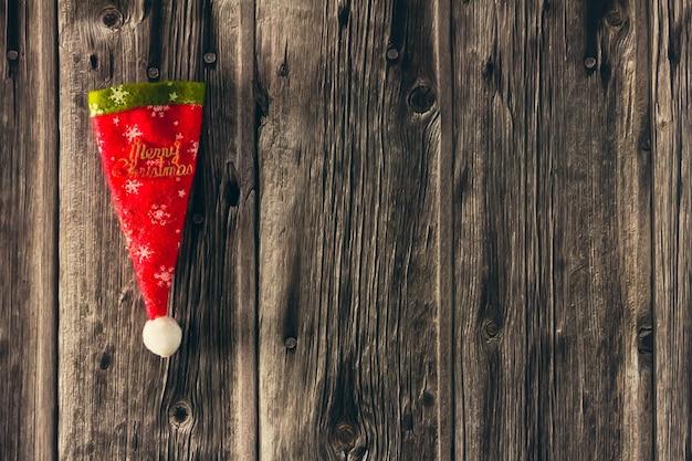 木製の背景に装飾的なクリスマスの帽子。スペースをコピーします。セレクティブフォーカス。