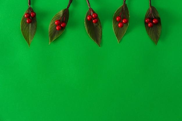 緑の背景に装飾的なクリスマスのヒイラギの葉。スペースをコピーします。セレクティブフォーカス。