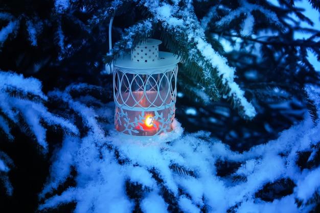 Декоративный рождественский фонарь с горящей свечой висит на заснеженной еловой ветке в зимнем парке. новогодняя праздничная открытка, плакат, дизайн открытки.