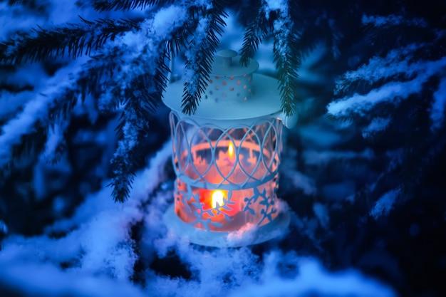 ウィンターパークの雪に覆われたモミの木の枝に燃えるろうそくがぶら下がっている装飾的なクリスマスランタン。新年のお祝いカード、ポスター、ポストカードのデザイン。