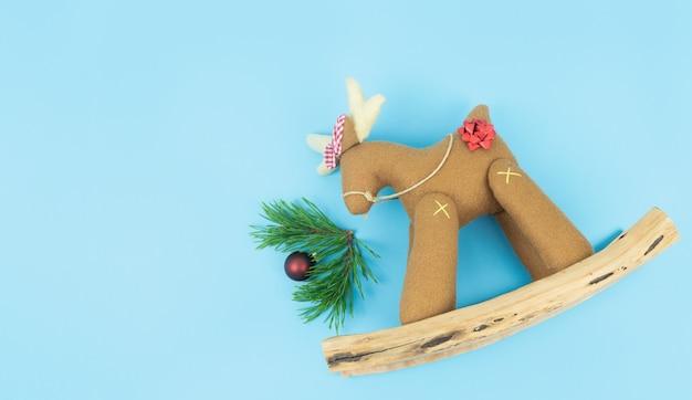 Декоративный рождественский олень с сосновыми ветками на синем фоне.