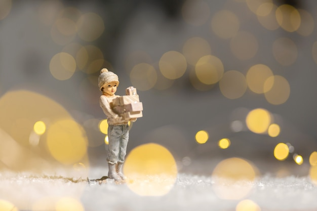 Decorative christmas-themed figurines. statuette of a girl holding boxes with gifts for christmas in her hands.