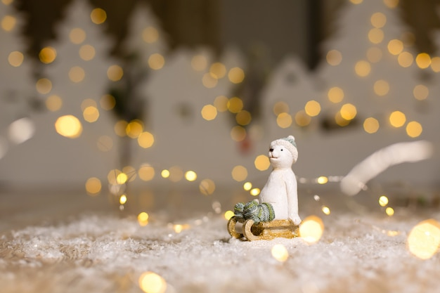 Decorative christmas-themed figurines. the statuette of a polar bear sits on a wooden sled, in a knitted hat and socks.