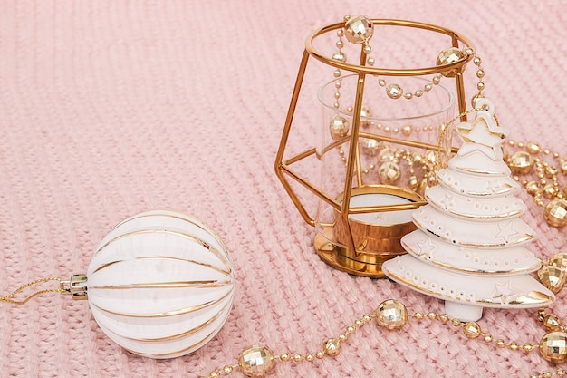 Decorative christmas tree, golden candlestick, bauble and gold garland on pink knitted background.