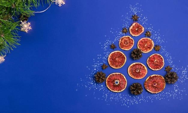 고전적인 파란색 배경 메리 크리스마스에 오렌지와 콘의 장식 크리스마스 트리