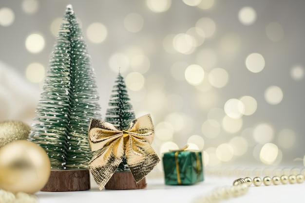 Decorative christmas trees decorated and gifts for the new year on the background of golden bokeh lights