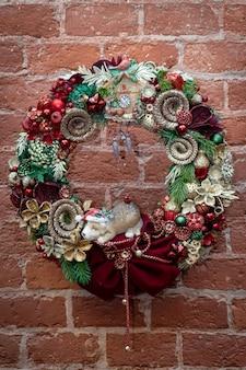 石積みの壁に掛かっている装飾的なクリスマスリース