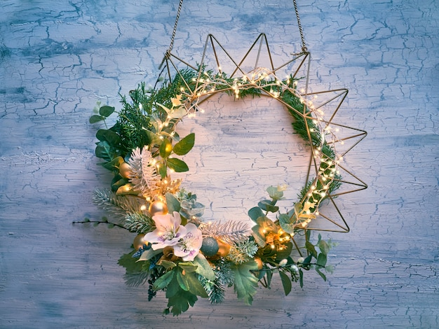 Decorative christmas wreath with fir, winter leaves and flowers on geometric golden metal frame with light garland