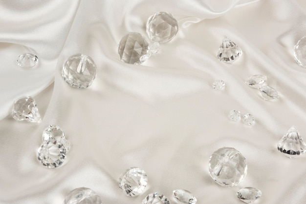 Decorative clear diamonds on white fabric textured background