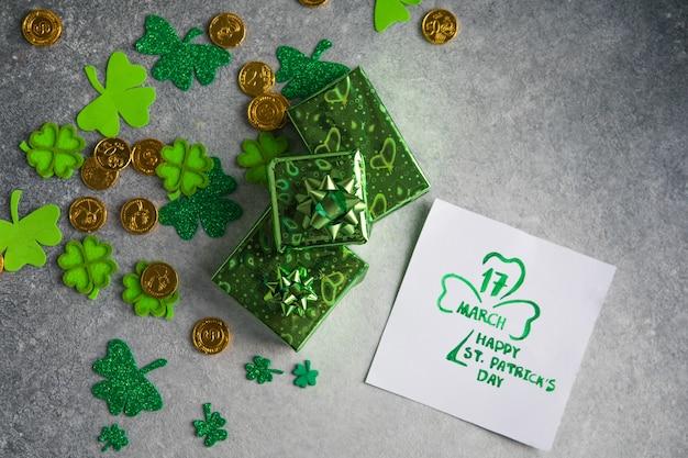 Декоративные листья клевера, зеленая подарочная коробка, монеты на каменном фоне, плоская планировка. празднование дня святого патрика. открытка с днем святого патрика