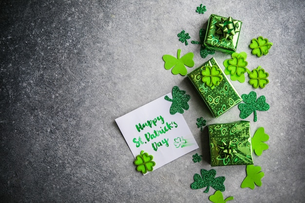 Decorative clover leaves, green gifts box, coins on stone background, flat lay. st. patrick's day celebration. card happy st. patrick's day