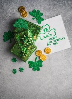 Декоративные листья клевера, зеленые подарки, монеты на каменном фоне, плоская кладка. празднование дня святого патрика