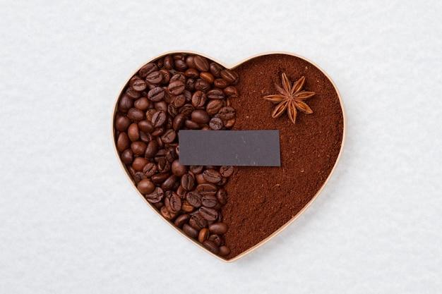 Декоративное кофейное сердце разделено на две части. чистый темный лист бумаги для copyspace. изолированные на белой поверхности